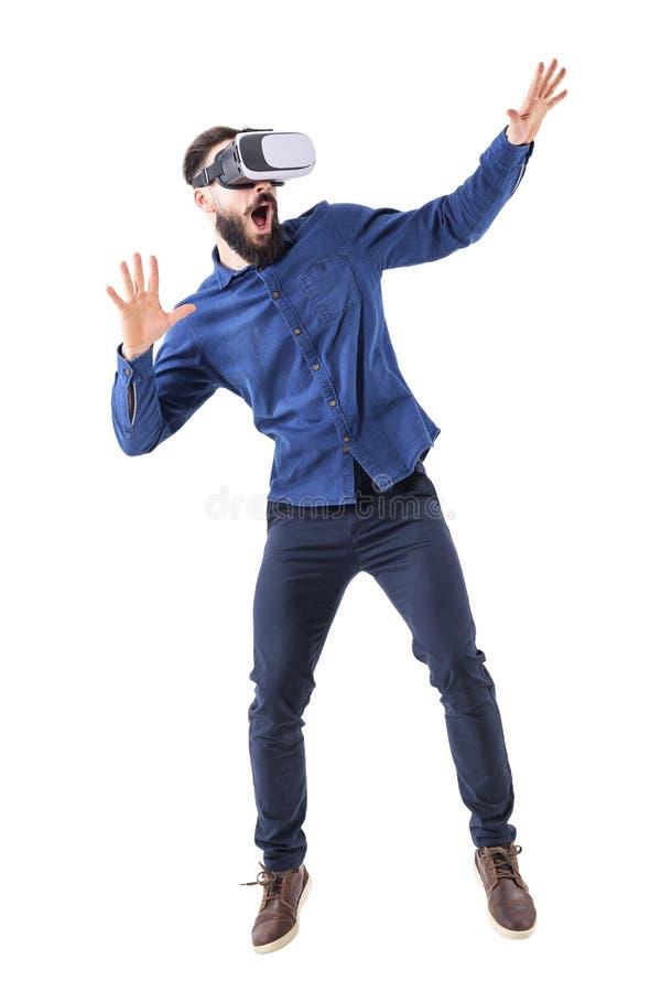 Scared ha colpito l'uomo adulto barbuto che ha esperienza della cuffia avricolare di realtà virtuale con la bocca aperta fotografie stock libere da diritti