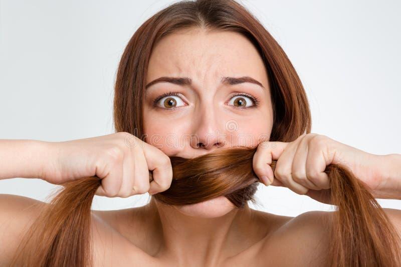 Scared ha spaventato la bocca coperta giovane donna con i suoi capelli lunghi immagine stock