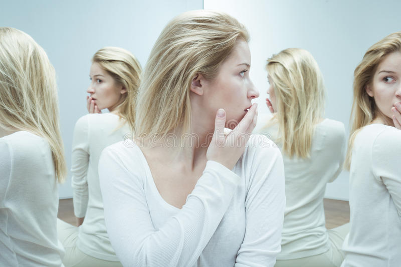 Scared of herself. Crazy young sick woman scared of herself royalty free stock photo