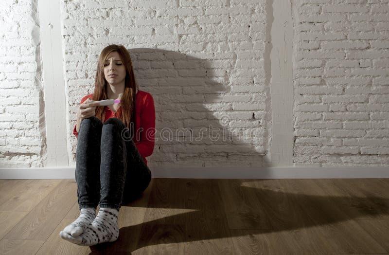 Scared a inquiété la fille enceinte d'adolescent ou la jeune femme désespérée tenant l'essai de grossesse positif images libres de droits