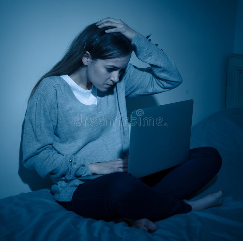 Sad teenager girl with laptop suffering bullying and harassment online. Cyberbullying concept. Scared and intimidated sad teenager bullied on line with laptop royalty free stock photos
