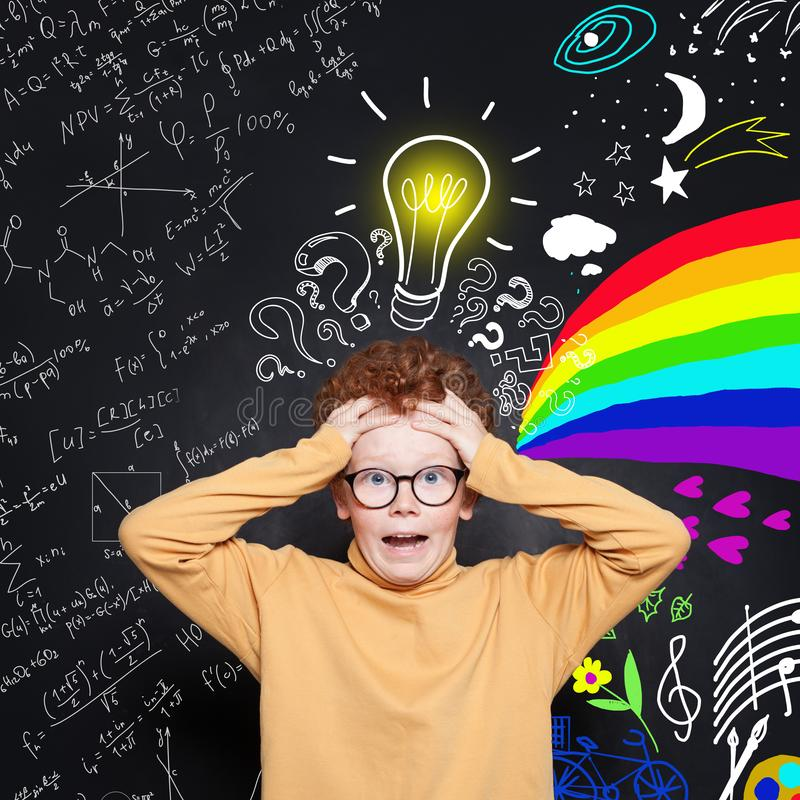 Scared kid with lightbulb. Education, brainstorming and idea concept. Cute redhead student boy on chalkboard background royalty free stock photo
