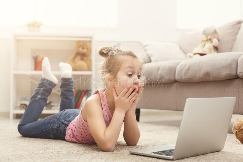 Scared casual little girl watching movie on laptop while lying on the floor at home royalty free stock images