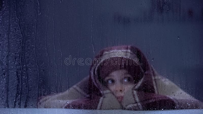 Scared little girl covered with blanket frightened by thunder on rainy day royalty free stock image