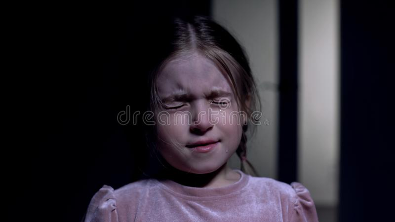 Scared little girl crying and closing eyes from fear, childhood phobias, closeup royalty free stock images