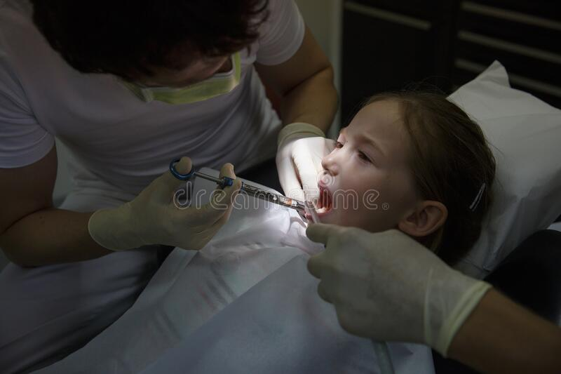 Scared little girl at dentist office, getting local anesthesia injection into gums, dentist numbing gums for dental work stock photos