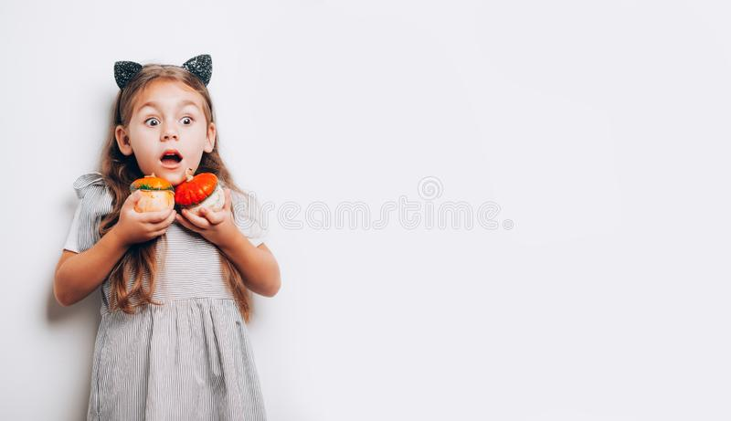 Scared little girl holding decorative pumpkins on white background royalty free stock image