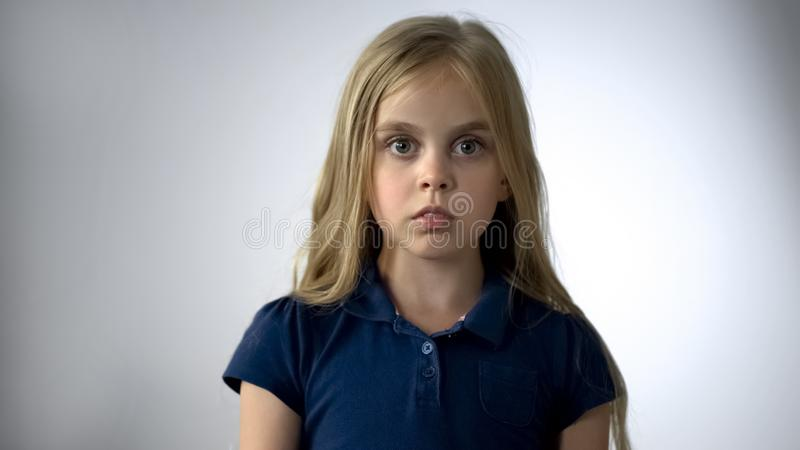 Scared little girl looking at camera with fear, children rights protection royalty free stock photo