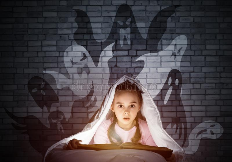 Scared little girl reading book in bed royalty free stock photo