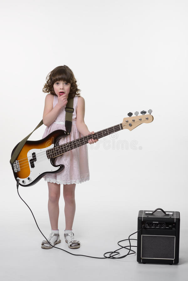 Scared little princess with guitar. Scared little princess with huge for her bass guitar. Opened mouth and big eyes. Small special amp in the corner. Small child stock photos
