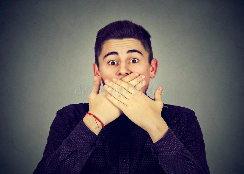 Scared man covering mouth with hands. Scared young man covering mouth with hands royalty free stock photo