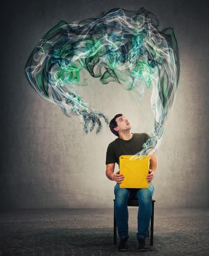 Scared man seated on a chair holding mystery box on knees looking up with shocked expression as a mystic dark smoke comes out of. The bin and transforms into a stock image