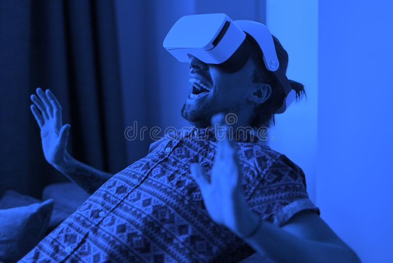 Scared man in VR headset on sofa. Toned image with blue color effect of terrified guy in VR helmet screaming and gesturing with hands while sitting on couch at royalty free stock photography
