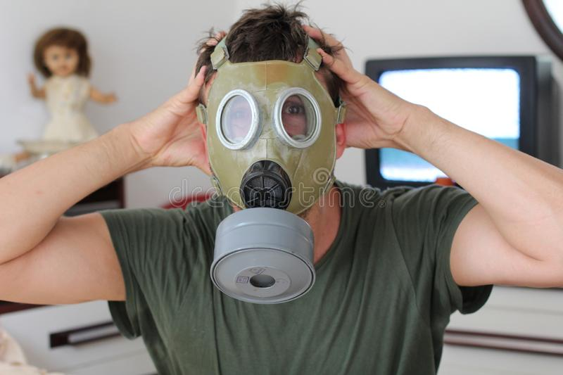 Scared man wearing gas mask at home stock images