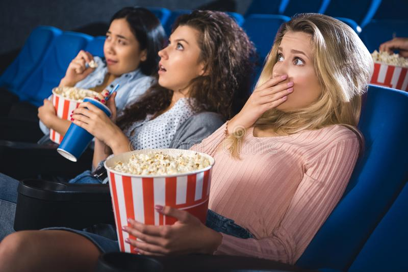 Scared multiracial women with popcorn watching film together. In movie theater stock photography