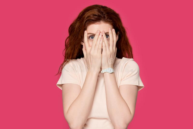 Scared redhead girl cover face peeking through fingers. Scared red-haired young woman isolated on pink studio background hide behind hands, terrified redhead stock photo