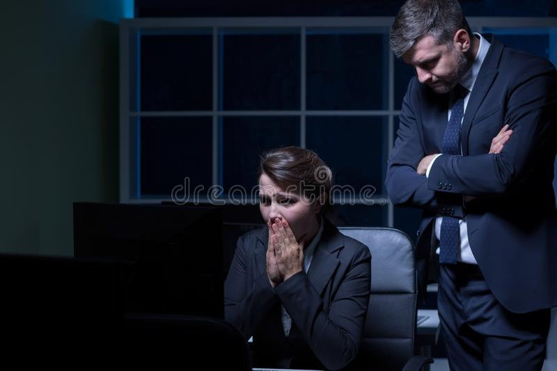 Scared secretary and cruel boss. Working overtime stock photos