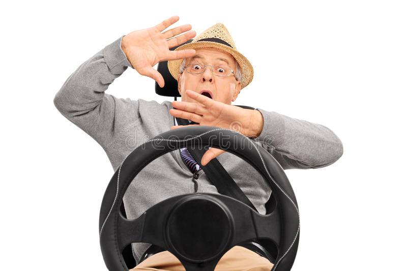 Scared senior sitting on a car seat and gesturing stock images