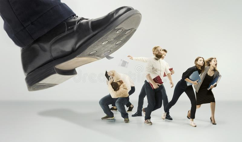 Scared and shocked team of young business men and women under boss pressure. Concept horror and fear of the boss. Collage with big shoe of boss stock images