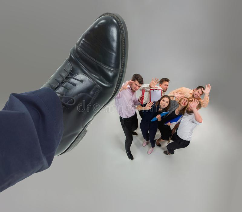 Scared and shocked team of young business men and women under boss pressure. Concept horror and fear of the boss. Collage with big shoe of boss royalty free stock images