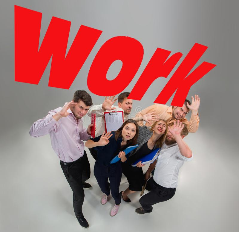 Scared and shocked team of young business men and women under world WORK pressure stock photography