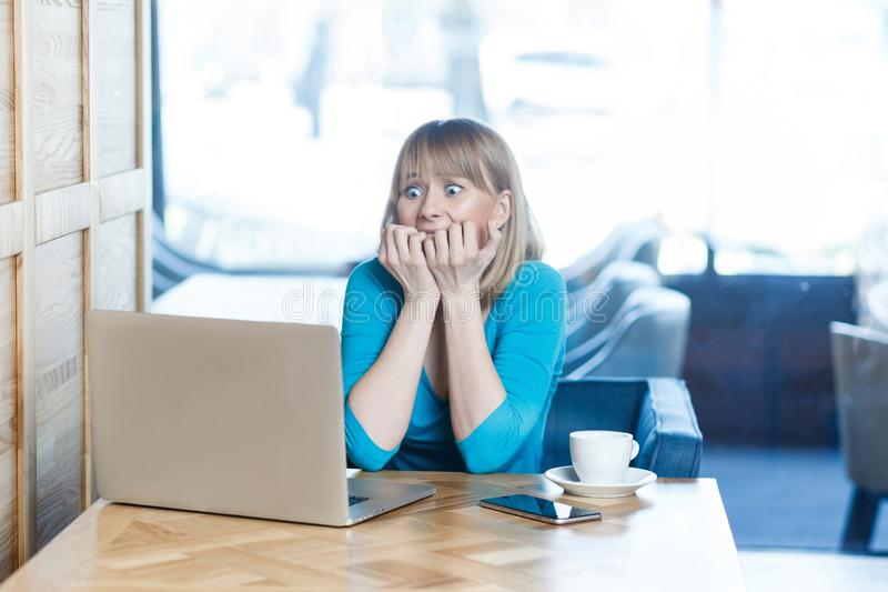 Scared! Side view portrait of emotional nervous young girl with blonde hear in blue blouse are sitting in cafe, working alone and stock photo