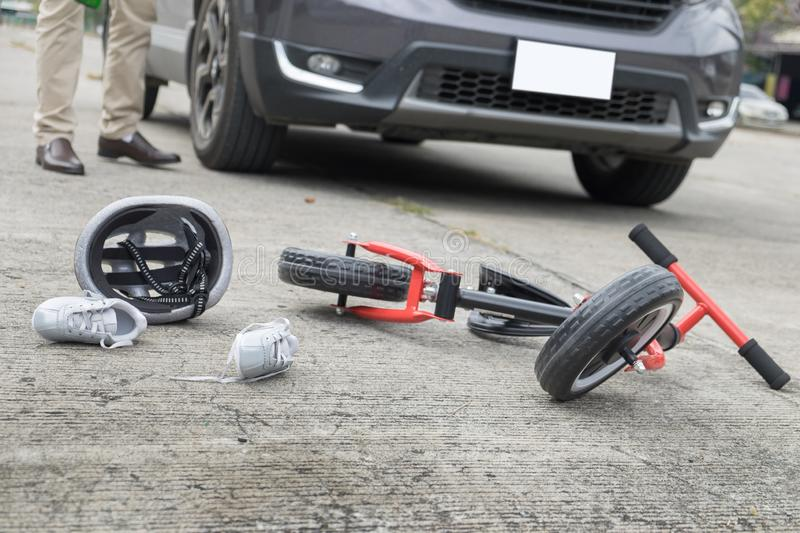 Scared and stressed desperate drunken driver and bottle of beer in front of automobile crash car with child bike after traffic acc royalty free stock photo