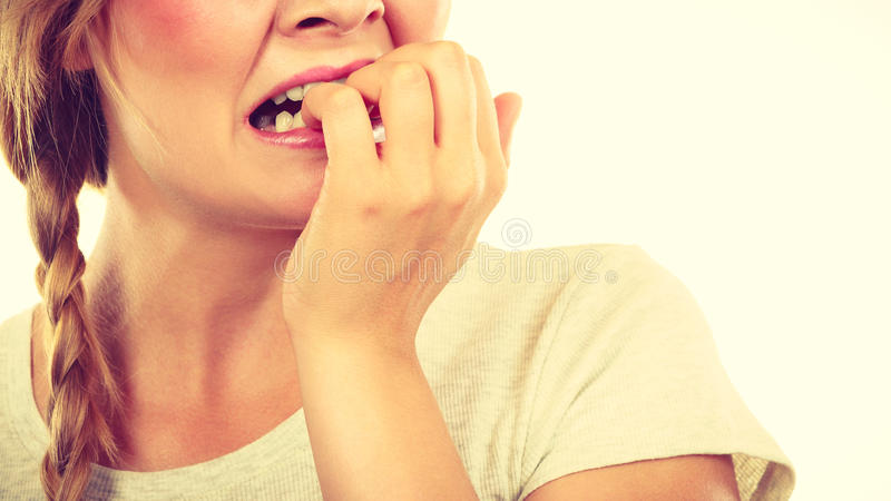 Scared, stressed woman biting her nails stock photo