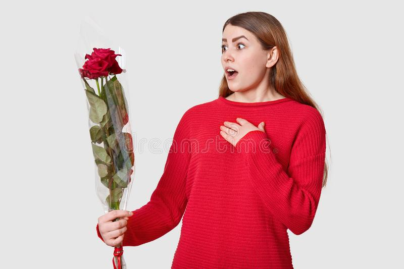 Scared surprised young European woman keeps hand on chest, looks with wonder at bouquet of red beautiful roses, wears casual stock photo