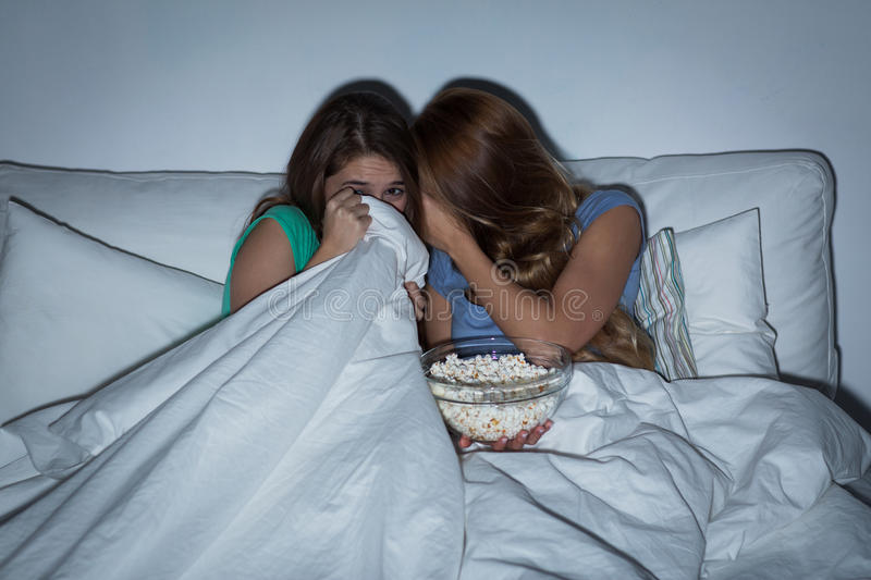 Scared teenage girls watching horror on tv at home. Friendship, people, pajama party, entertainment and junk food concept - scared friends or teenage girls royalty free stock photography