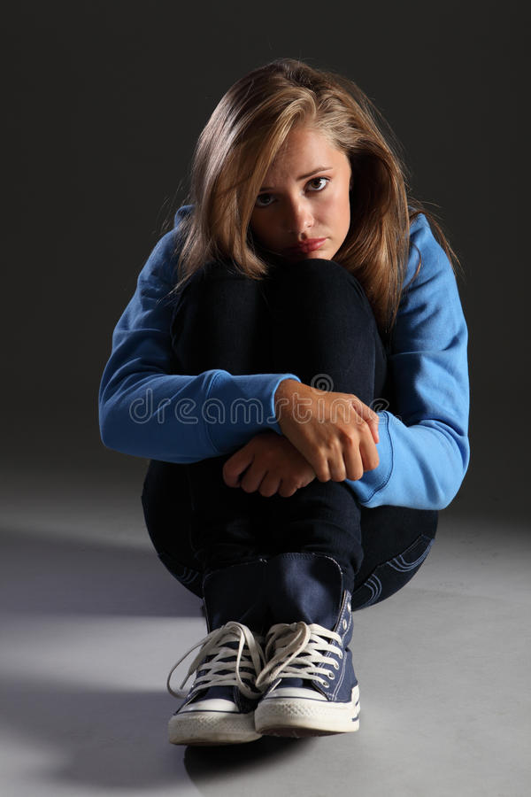 Scared teenager girl on floor stressed and alone. Sad frightened young teenager girl sitting on floor chin on knees looking scared and alone with big tearful stock photo