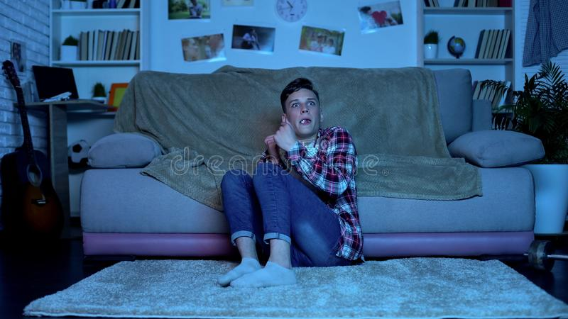 Scared teenager watching horror movie late at night, eating popcorn, emotions royalty free stock images