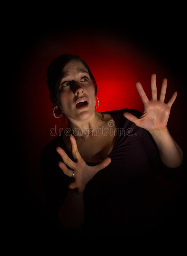 Scared woman on dark background royalty free stock photos