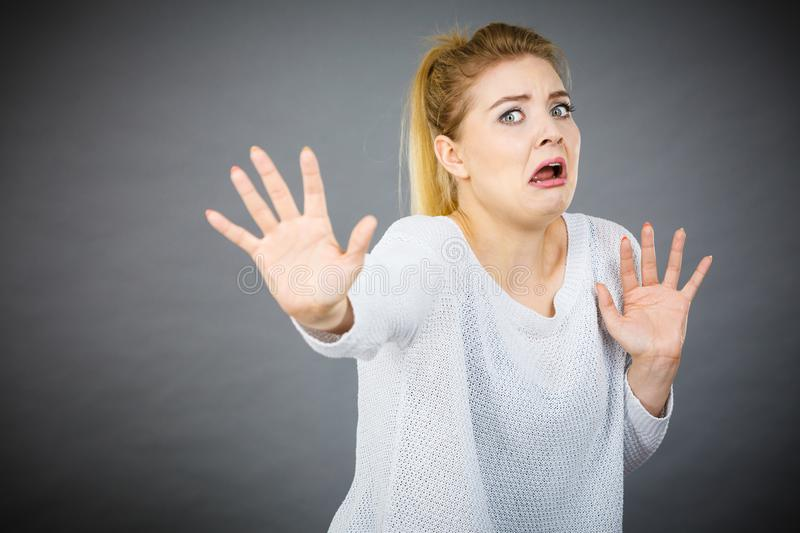 Scared woman gesturing stop gesture with hands stock photo