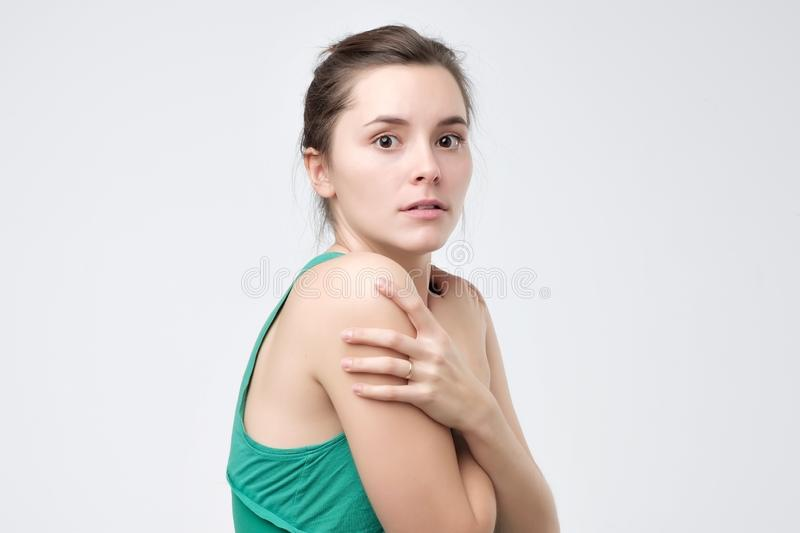 Scared woman in green clothes looking nervously aside feeling distrust or fear. While posing against white background stock photography