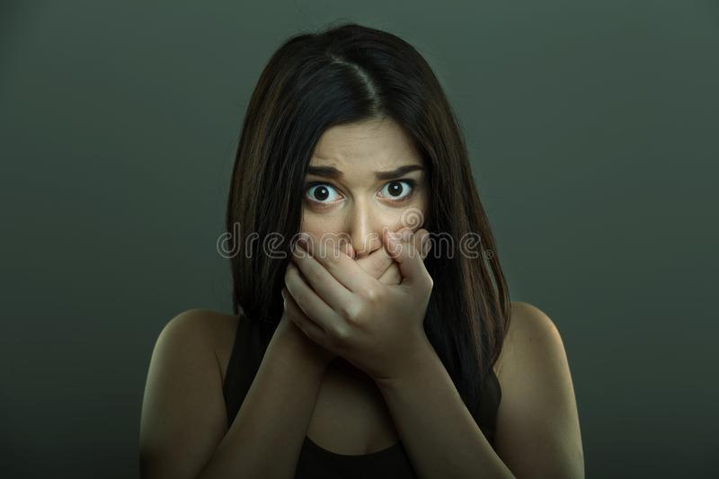 Scared woman with hands covering mouth stock photo