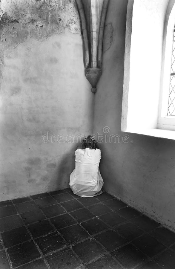 Scared woman. Scared, insane woman hiding in a corner of an ancient building royalty free stock photos
