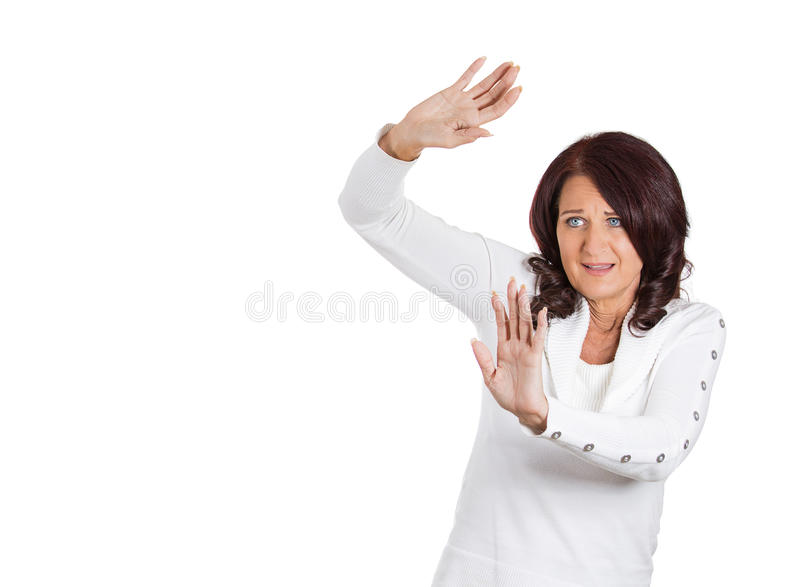 Scared woman trying to protect herself arms raised up in defense royalty free stock photography