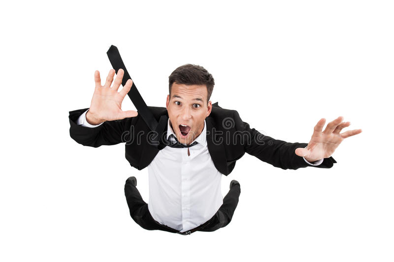 Scared young businessman in falling position. royalty free stock images