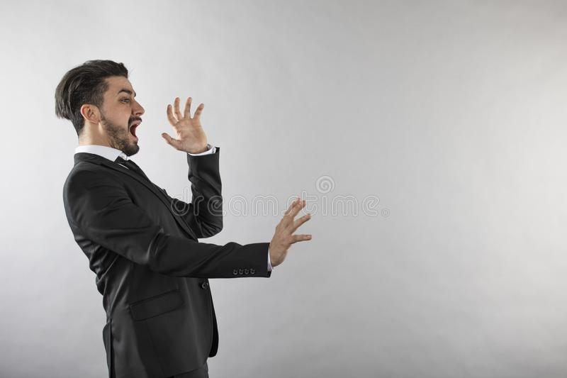 Scared young businessman pulling back from something. On white background stock images
