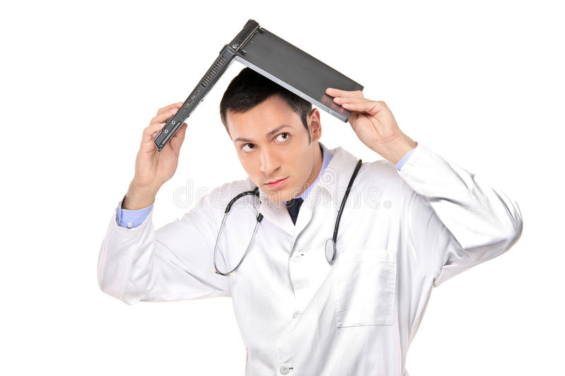 Scared young doctor covering his head royalty free stock image