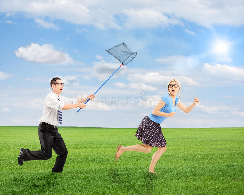 Scared young female trying to runaway from man with net. Scared young female trying to runaway from men running with butterfly net outdoor, shot with a tilt and stock photography