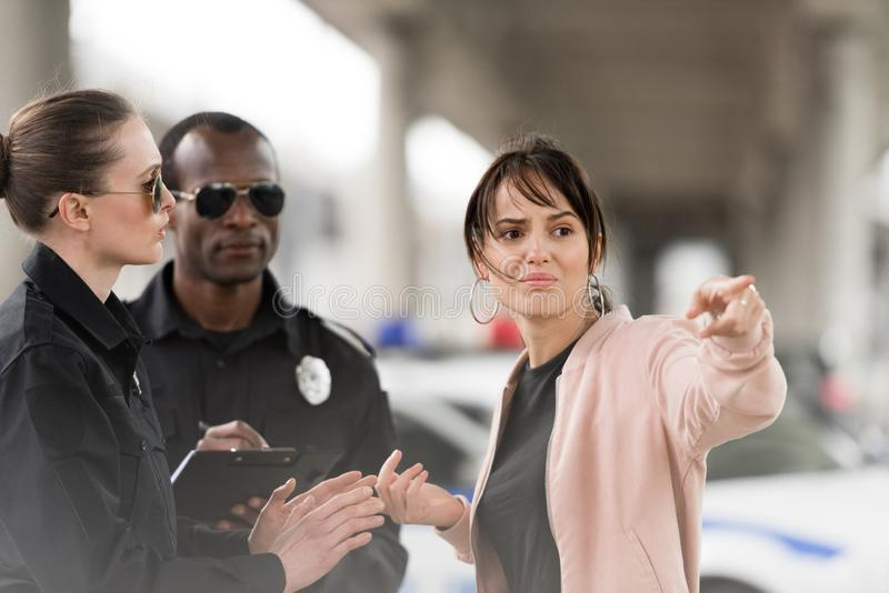 Scared young female victim pointing by finger to policewoman. And african american policeman writing in clipboard stock image