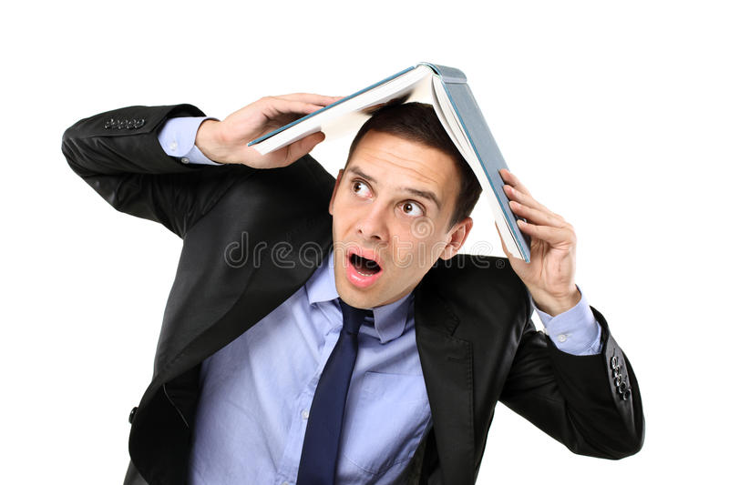 Scared Young Man Covering His Head With A Book Stock Photo
