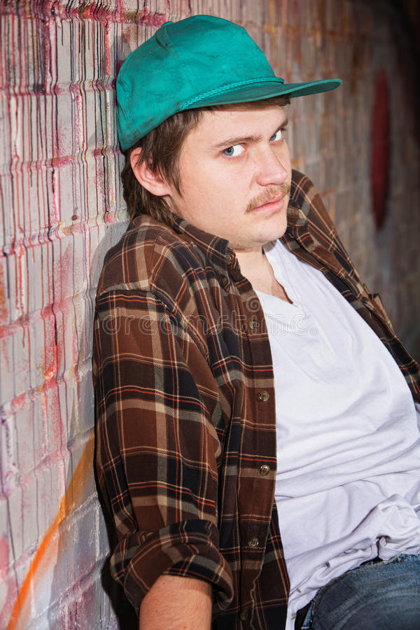Scared Young Man. In hat leaning against a wall stock photo