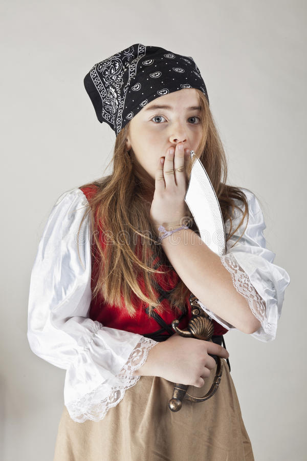 Scared young pirate girl in a costume royalty free stock photography