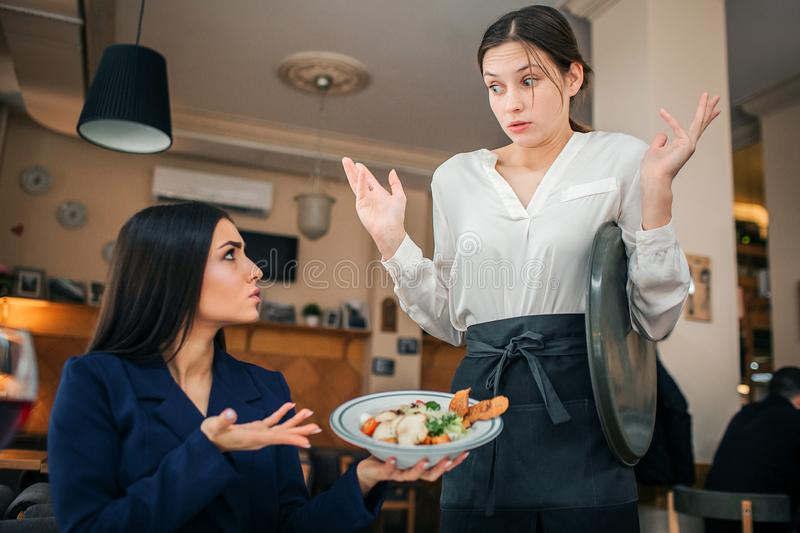 Scared young waitress look at salad bowl brunette hold in hands. She show her this food. Young woman in blouse is royalty free stock image