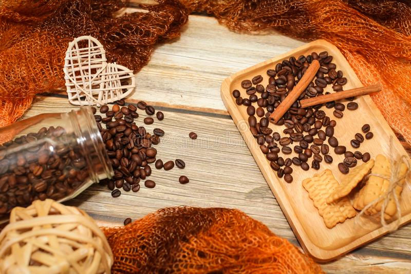 Scarf, glass jar, cookies, cinnamon sticks and scattered coffee beans on vintage wooden table. Top view. Coffee break. royalty free stock photos