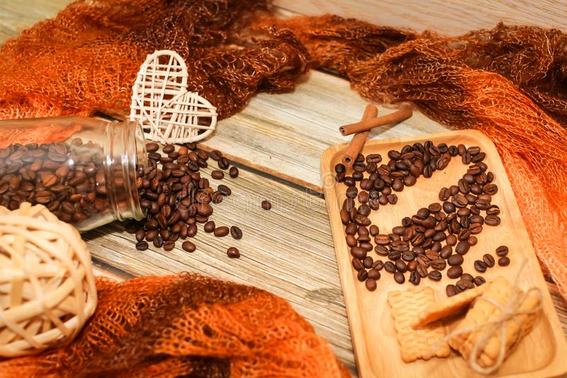 Scarf, glass jar, cookies, cinnamon sticks and scattered coffee beans on vintage wooden table. Top view. Coffee break. royalty free stock image