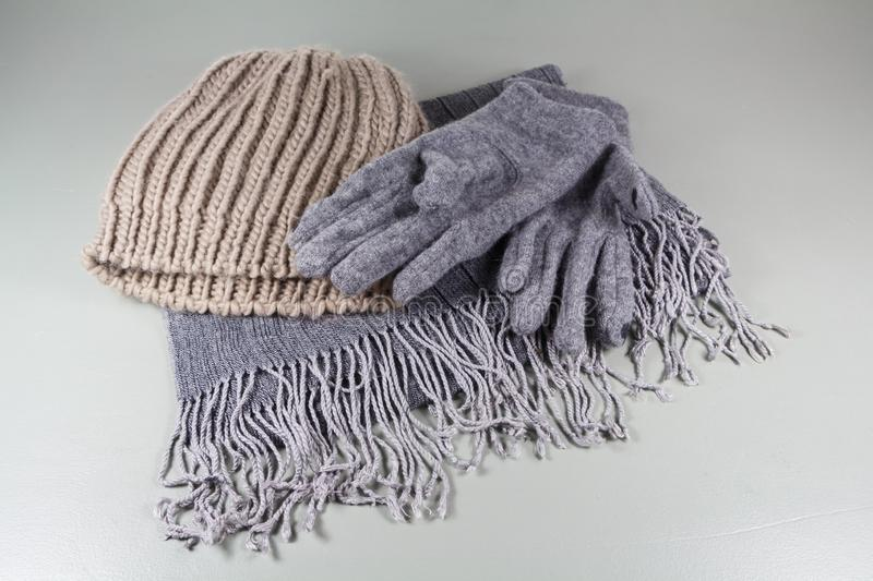 Scarf, gloves and beanie. Gray scarf in cotton, gray gloves and beige beanie in wool royalty free stock photo